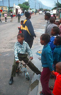 Cape Town Townships street scene with kids and bicycle