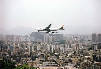 A Jumbo Jet approaches Kai-Tak Airport in Hong Kong